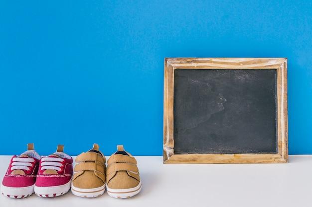 Concetto di bambino con ardesia e due paia di scarpe