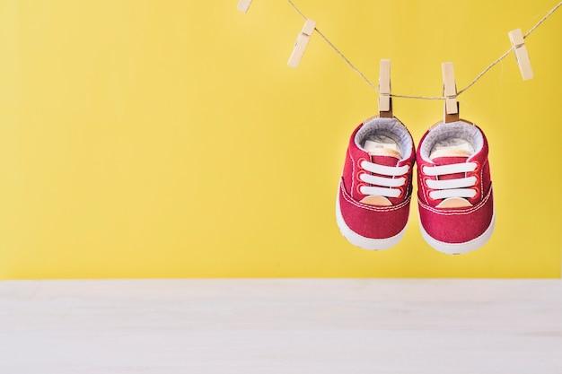 Concetto di bambino con le scarpe sul clothesline