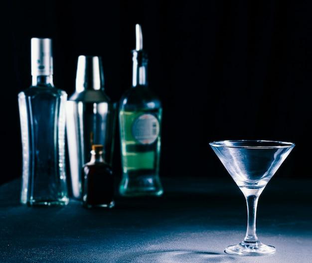 Concetto di bar. alcol in bottiglia, shaker e bicchiere da cocktail. copia spazio.