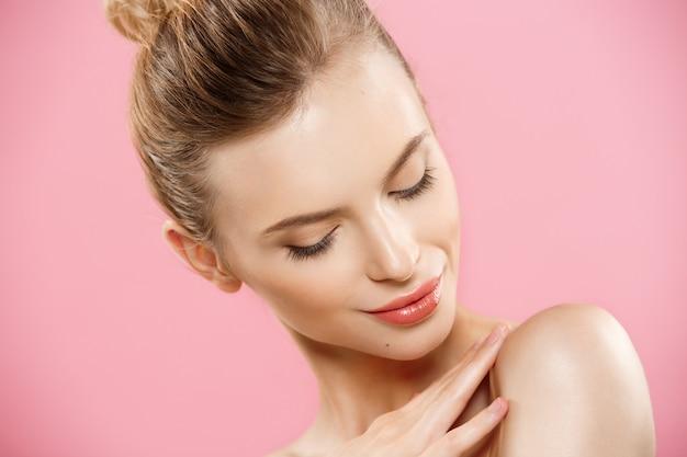 Concetto di bellezza - bella donna caucasica con la pelle pulita, make-up naturale isolato su sfondo rosa brillante con spazio di copia.