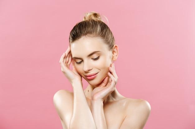 Concetto di bellezza - bella donna con la pelle pulita fresca vicino sullo studio rosa. volto di cura della pelle. cosmetologia.