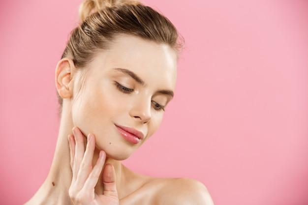 Concetto di bellezza - close up ritratto di attraente ragazza caucasica con la bellezza della pelle naturale isolato su sfondo rosa con copia spazio.