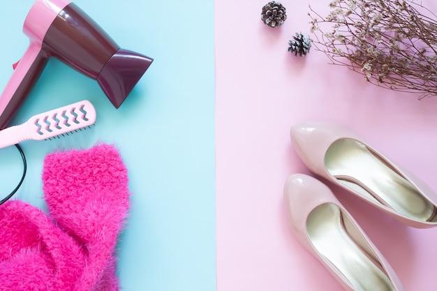 Concetto di bellezza con asciugacapelli e donna essentials su sfondo di colore pastello