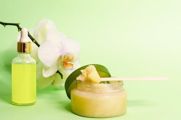 Concetto di bellezza. cosmetici naturali di lusso per la cura di viso e corpo, scrub, peeling con zucchero o sale, olio con vitamina c sulla parete verde, spazio di copia