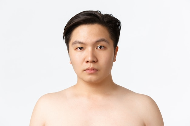 Concetto di bellezza, cura della pelle e igiene. primo piano di giovane uomo asiatico con pelle incline all'acne, in piedi nudo sopra il muro bianco, pubblicità di prima dopo aver usato detergenti per la pelle, muro bianco
