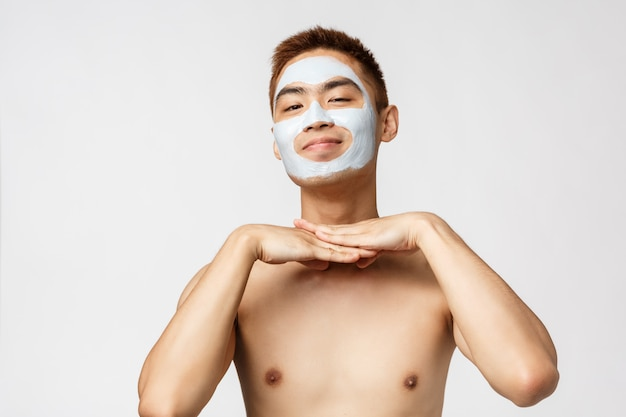 Concetto di bellezza, cura della pelle e spa. ritratto di uomo asiatico nudo adorabile e sciocco, sorridente soddisfatto, indossando la crema per la maschera facciale, prodotto cosmetico prendersi cura della pelle, in piedi muro bianco