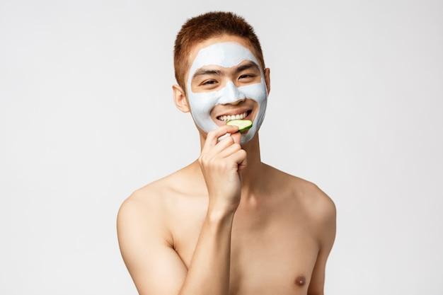 Concetto di bellezza, cura della pelle e spa. uomo asiatico bello con il torso nudo nella maschera facciale cosmetica, mangiando cetriolo e sorridendo, rilassandosi sullo svago al salone, stando parete bianca