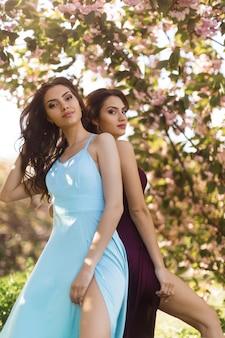 Concetto di bellezza di primavera. adatti un ritratto di due donne vicino all'albero sbocciante sulla natura