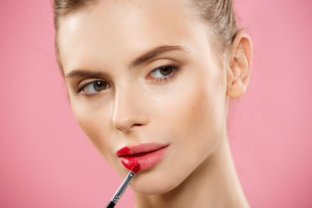 Concetto di bellezza - donna che applica rossetto rosso con sfondo studio rosa. bella ragazza fa il trucco.