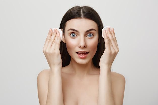 Concetto di bellezza e cosmetologia. donna emozionante che tiene i dischetti di cotone, mascara wash-off