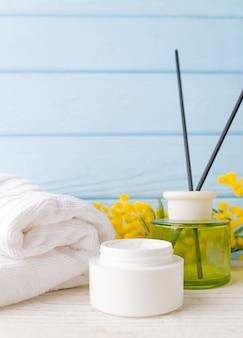Concetto di bellezza e moda con set spa. crema, asciugamano e fiori gialli e bastoncini di incenso.