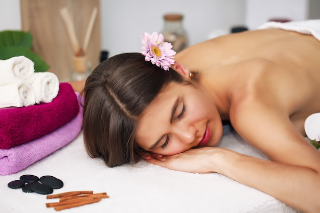 Concetto di bellezza e spa - donna felice nel salone della stazione termale che si trova sulla scrivania di massaggio