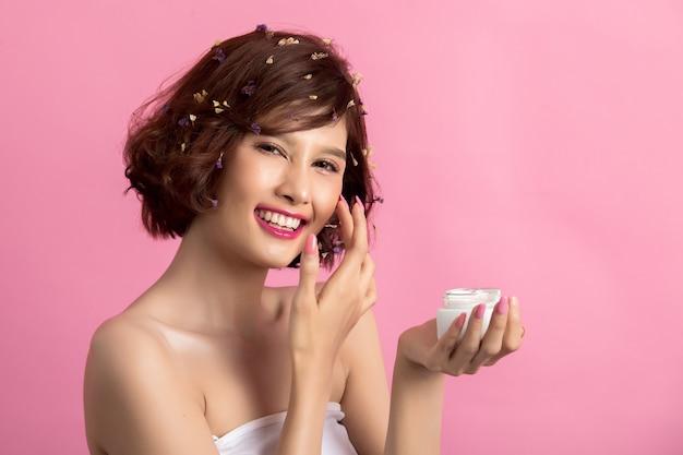 Concetto di bellezza la donna tiene una crema idratante in mano