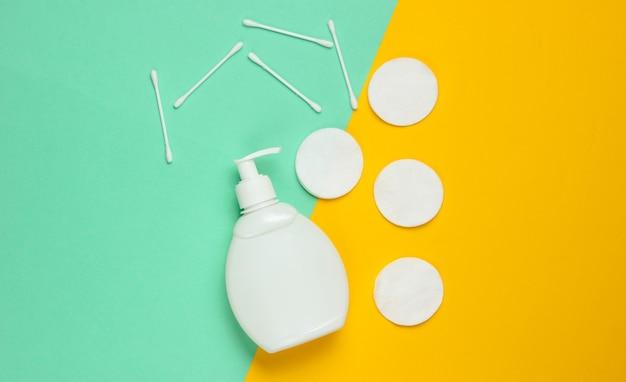 Concetto di bellezza minimalista. crema per bottiglie, tamponi di cotone, bastoncini per le orecchie su sfondo blu-giallo.