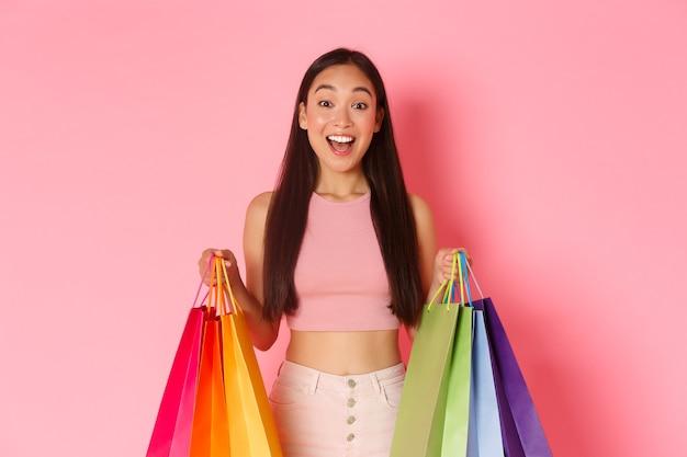 Concetto di bellezza, moda e stile di vita. primo piano della ragazza asiatica graziosa divertita ed eccitata con le borse della spesa, colpita da molti sconti e vendite nei negozi, muro rosa.