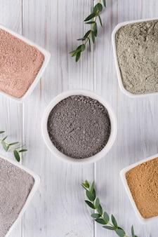 Concetto di bellezza. piante piatte, diversi tipi di polveri di fango argilloso per maschera o scrub viso e corpo fatti in casa