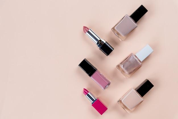 Concetto di bellezza. set di cosmetici trucco professionale su sfondo pastello. set di cosmetici. oggetti cosmetici decorativi, flaconi per unghie, rossetto. copi lo spazio