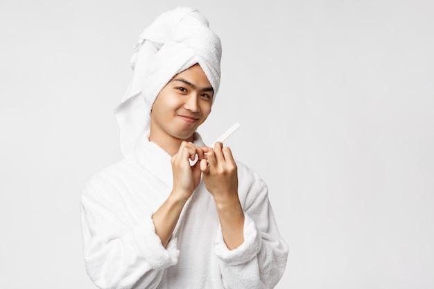 Concetto di bellezza, spa e tempo libero. ritratto di sciocco bell'uomo asiatico in accappatoio e telo da bagno, sorridendo compiaciuto, lucidando le unghie e fare la manicure, in piedi muro bianco