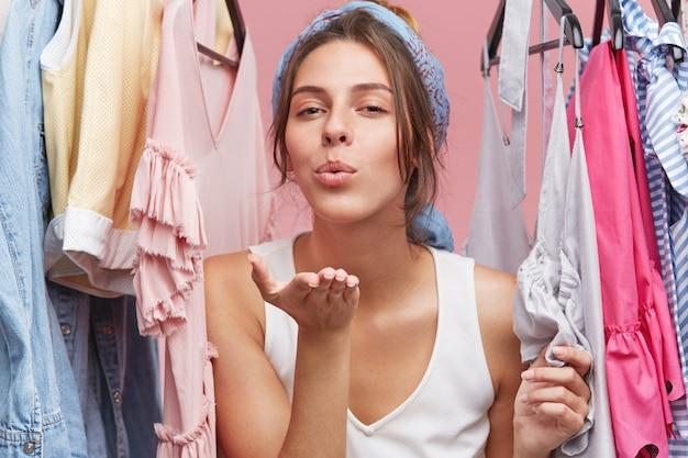 Concetto di bellezza, stile, moda, abbigliamento e shopping. bella fiduciosa giovane femmina in bianco a-shirt gettando un bacio