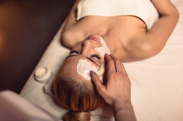 Concetto di benessere con donna con crema in faccia