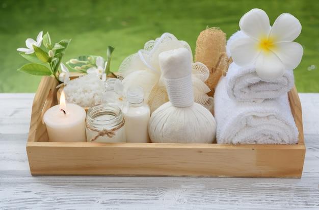 Concetto di benessere della stazione termale, candela bianca, sapone del latte, sale, asciugamano, fiori e palla di massaggio di erbe sulla tavola di legno bianca