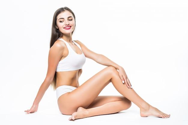 Concetto di benessere e bellezza. bella donna esile in biancheria intima bianca che si siede sul pavimento bianco