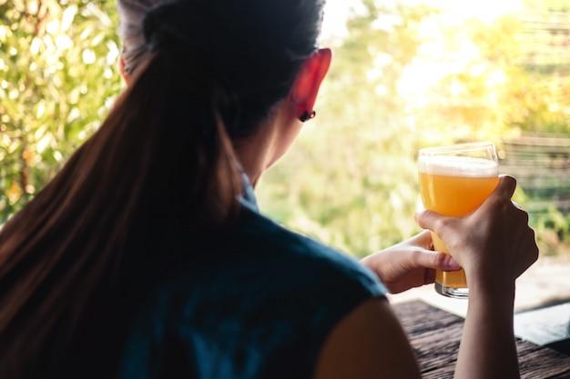 Concetto di bere birra femminile. donna che si rilassa da un bicchiere di birra in estate