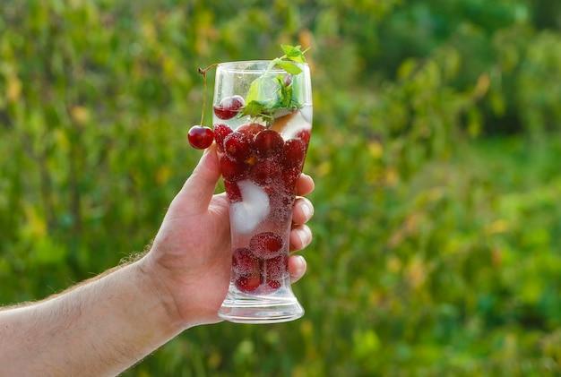Concetto di bevanda sana sulla vista laterale di sfondo verde. mano che tiene un bicchiere di cocktail.