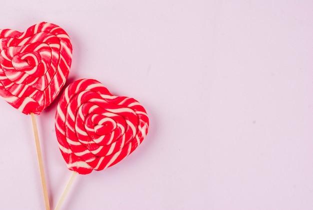 Concetto di biglietto di auguri sfondo rosa chiaro di san valentino due lecca-lecca cuore rosso o caramelle dolci su bastoni