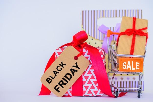 Concetto di black friday. carrello e contenitore di regalo su fondo bianco.