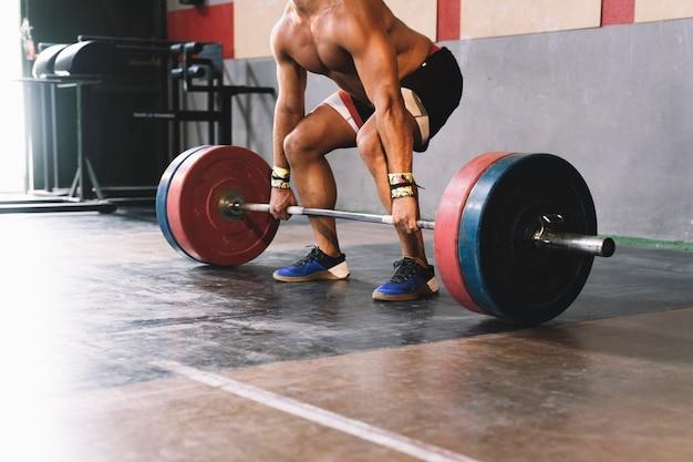 Concetto di bodybuilding con barbell di sollevamento del tiratore