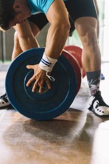 Concetto di bodybuilding con uomo e piastre di peso