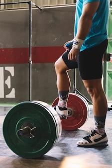 Concetto di bodybuilding vista laterale con l'uomo mettere piede sul barbell