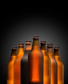 Concetto di branding e marketing per la birra con una linea di bottiglie marroni vuote piene senza etichetta non aperte su uno sfondo scuro e oscuro concettuale dell'oktoberfest o della vita notturna