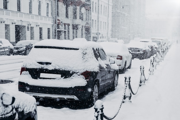 Concetto di bufera di neve, forti nevicate o bufera di neve. fila di automobili coperte di neve durante il clima invernale innevato