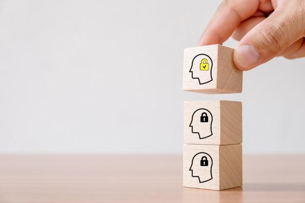 Concetto di business di idea creativa e innovazione. blocco cubo in legno raccolto a mano con sblocco testa umana