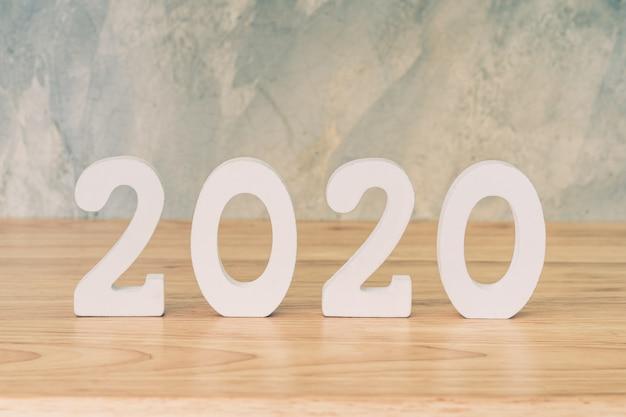Concetto di business e design - numero di legno 2020 per happy new year testo sul tavolo di legno.