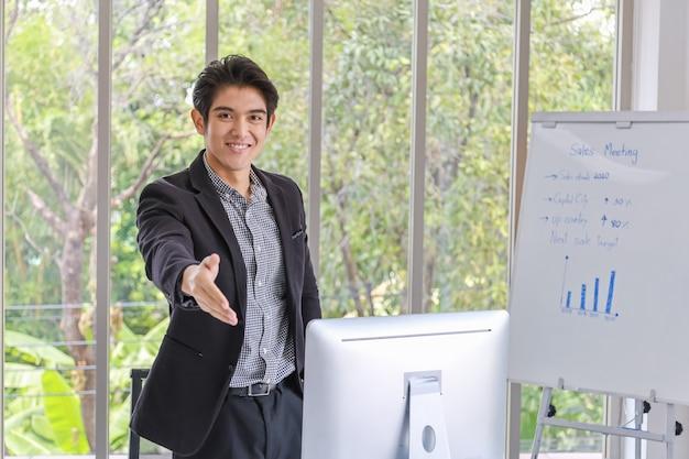 Concetto di business e meeting. ritratto della mano aperta del giovane uomo d'affari asiatico astuto sorridente felice per la stretta di mano nell'ufficio.
