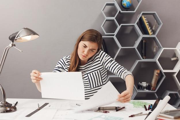 Concetto di business, freelance, lavoro di squadra. giovane bello architetto femminile confuso che si siede nel posto di coworking, parlando al telefono con il cliente, cercando di trovare informazioni nei documenti.