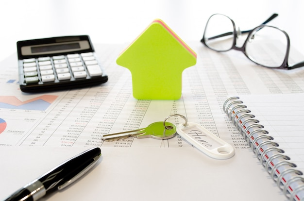 Concetto di business per l'acquisto o il risparmio per una casa con, calcolatrice, occhiali da vista, penna, chiavi, forma della casa e documenti. vista laterale.