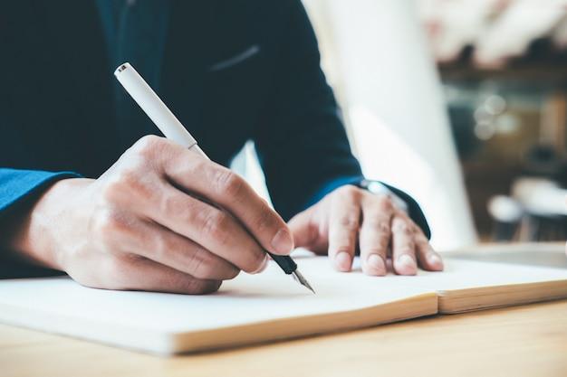Concetto di business taccuino di scrittura dell'uomo d'affari