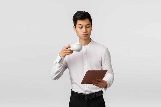 Concetto di business, tecnologia e finanza. imprenditore di sesso maschile dall'aspetto serio ed elegante, di successo, che legge le notizie in tavoletta digitale, beve il caffè dalla tazza, studia i documenti online