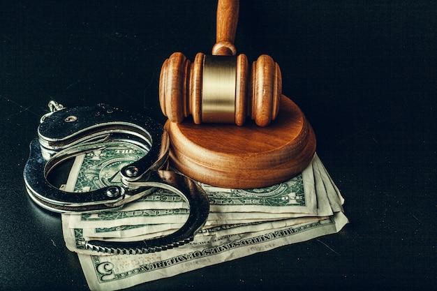 Concetto di bustarella. banconote, manette e martelletto del dollaro sul tavolo nero scuro