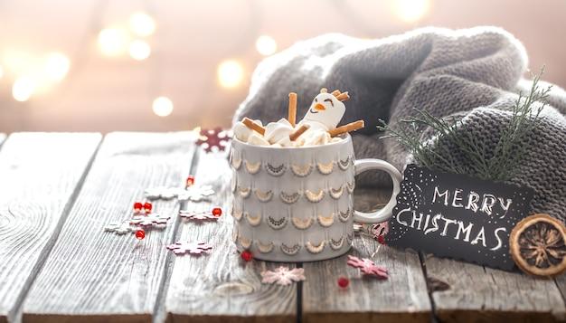 Concetto di cacao di natale con marshmallow su uno sfondo di legno in un'atmosfera festosa e accogliente