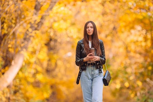 Concetto di caduta - bella donna nel parco di autunno sotto il fogliame di caduta