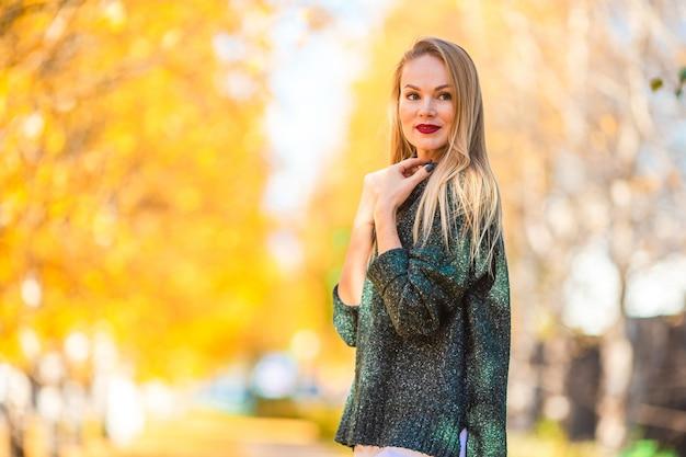 Concetto di caduta - caffè bevente della bella donna nel parco di autunno sotto il fogliame di caduta