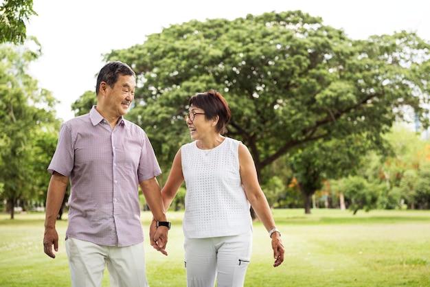 Concetto di camminata del parco delle coppie asiatiche senior