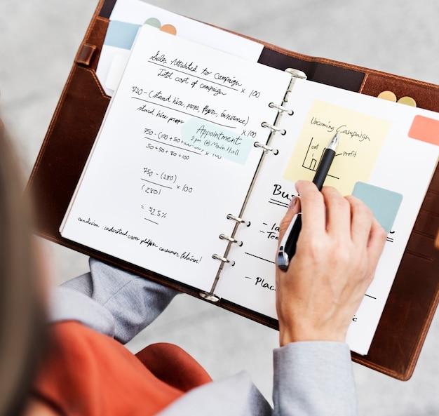 Concetto di campagna di marketing del taccuino di planning writing della donna di affari