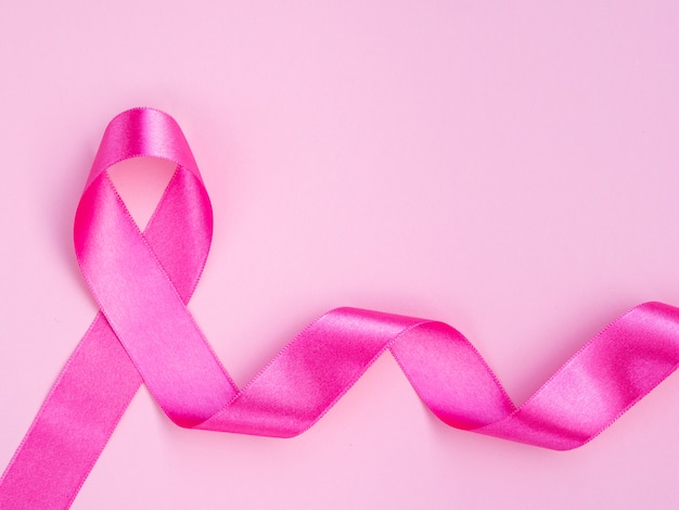 Concetto di cancro al seno piatto disteso con nastro