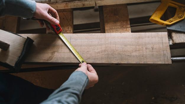 Concetto di carpenteria con misurazione dell'uomo